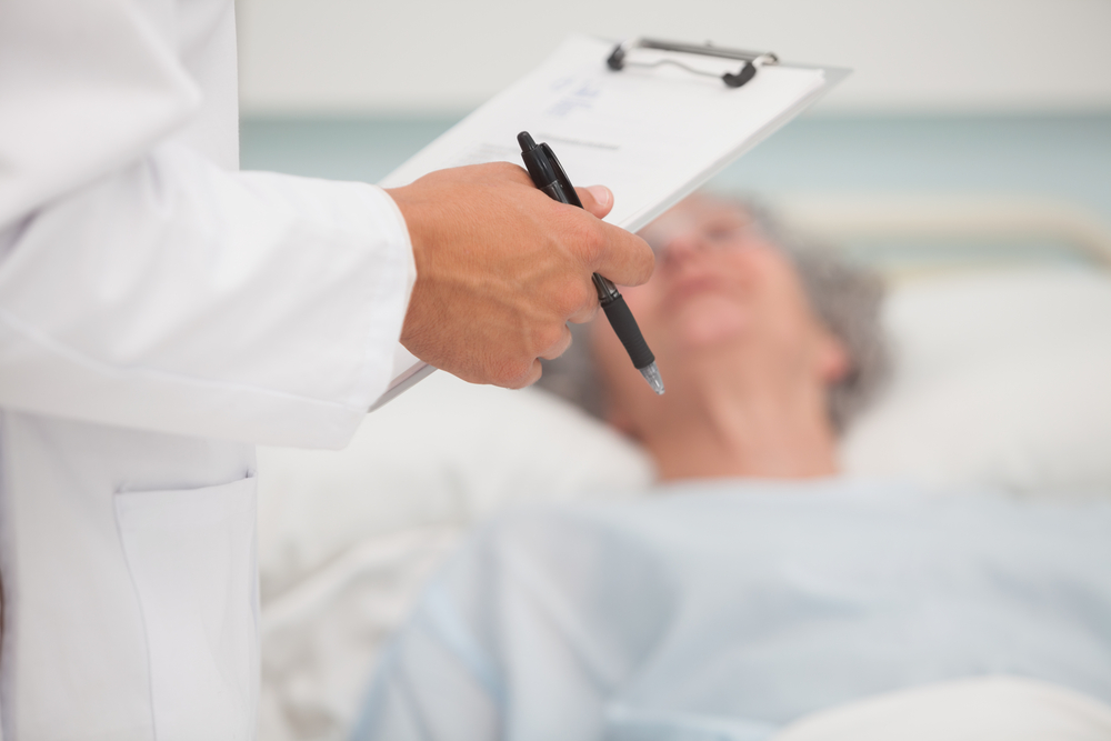 Doctor holding clipboard with elderly lady lying in hospital bed