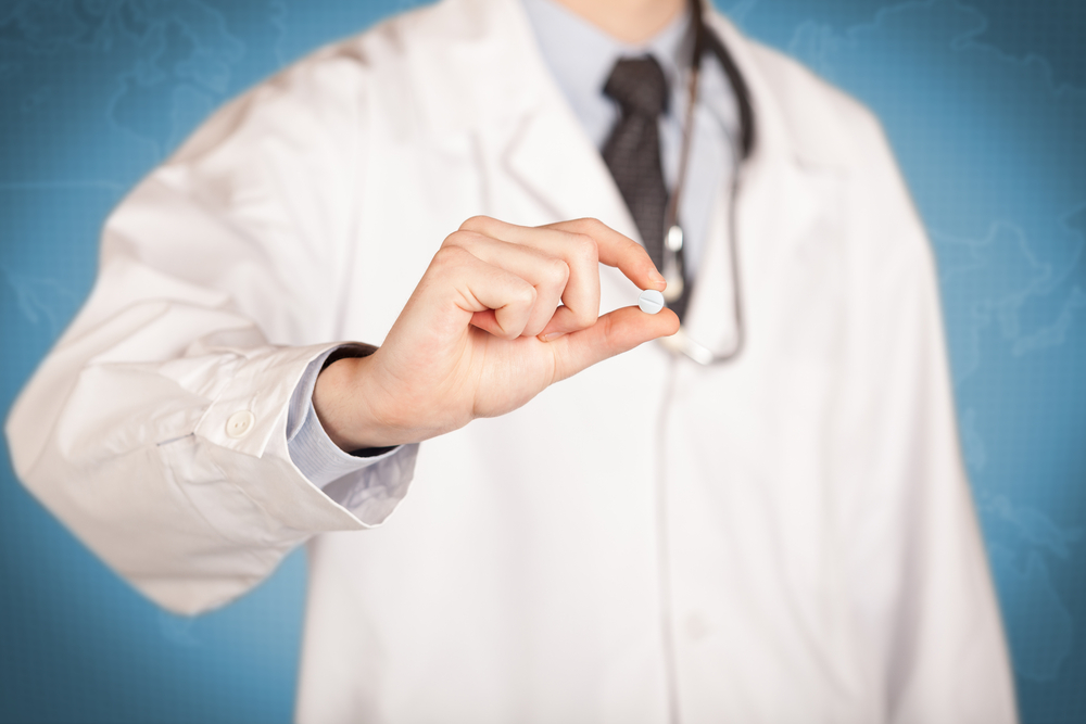 A male doctor in white coat in front of a blue wall, with a stethoscope on one shoulder holding a pill between his fingers