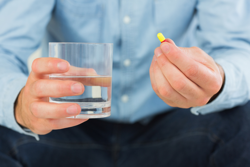 Close up of man holding a pill and glass of water in bright living room-1