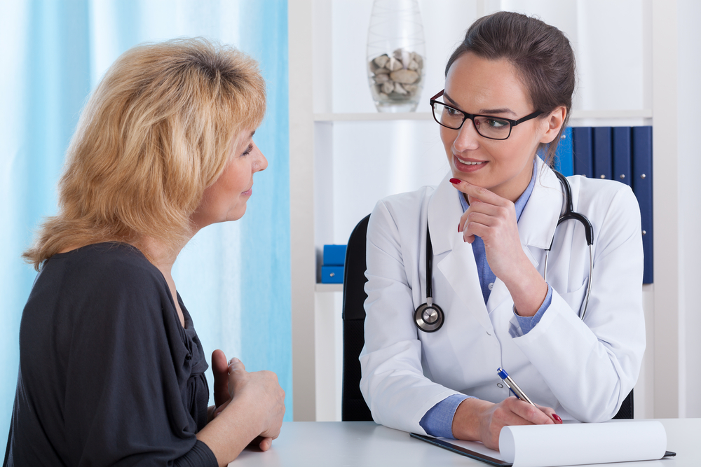 Doctor and middle aged patient talking to each other during visit in the office-1