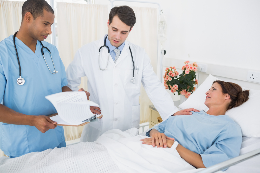 Doctor and surgeon visiting female patient in the hospital