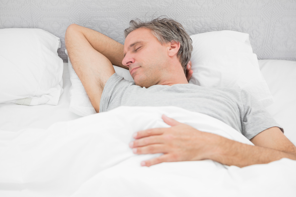 Man sleeping soundly in his bed at home-1