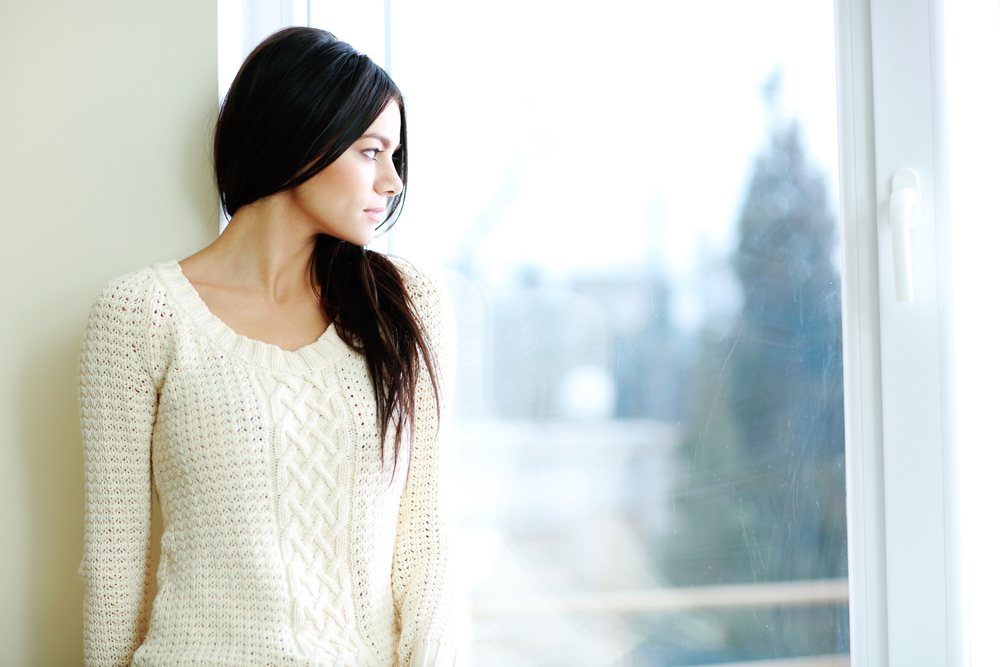 Portrait of a young beautiful woman looking at window