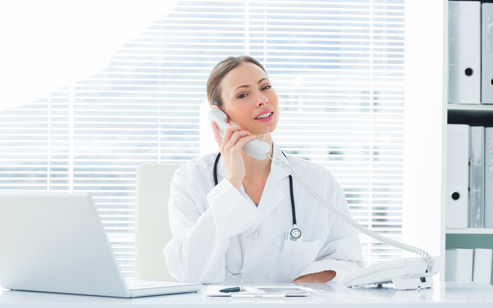 Portrait of confident female doctor using telephone at desk in clinic
