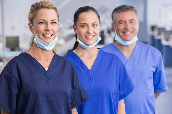 Portrait of smiling co-workers standing in a line in dental clinic-1
