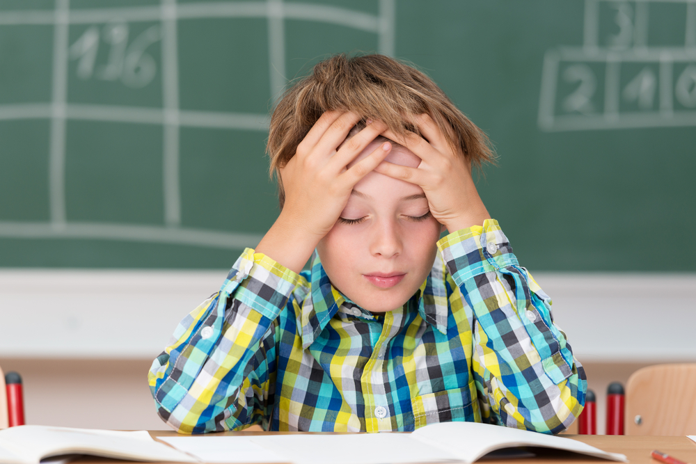 Young boy concentrating on his schoolwork sitting at his desk in the classroom with his head in his hands reading his class notes-1