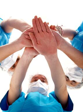 doctors with hands together to form a medical teamwork - isolated over a white background