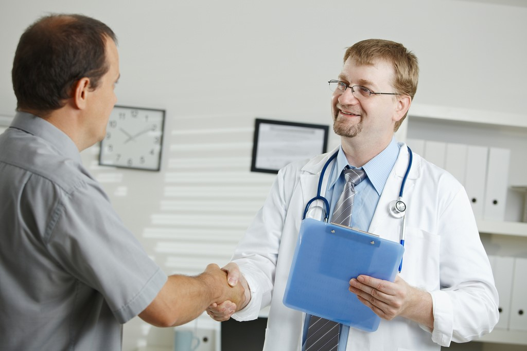 Doctor in white lab coat shaking patients hand